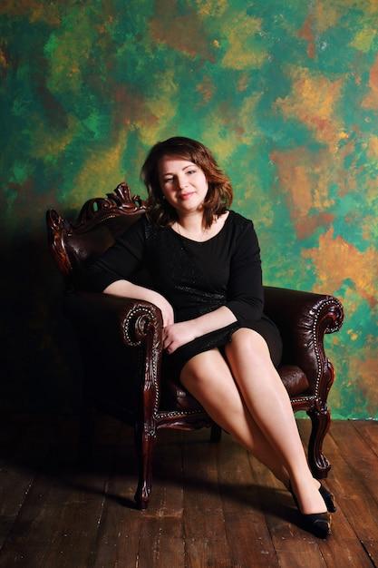 Uma mulher sentada em uma cadeira Foto Premium