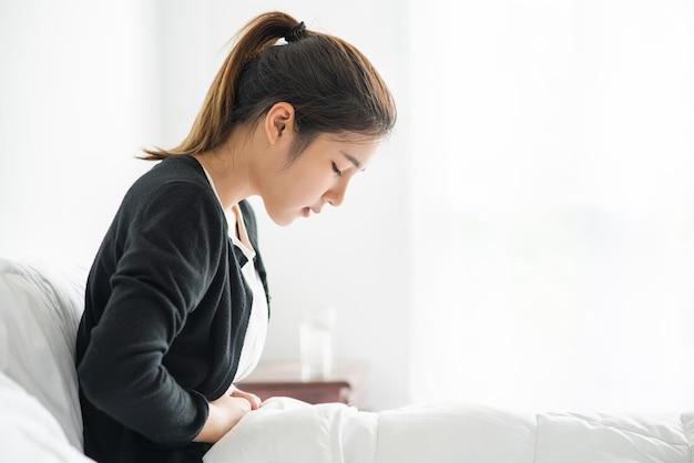 Uma mulher sentada na cama com dor abdominal e pressionando a mão na barriga. Foto gratuita