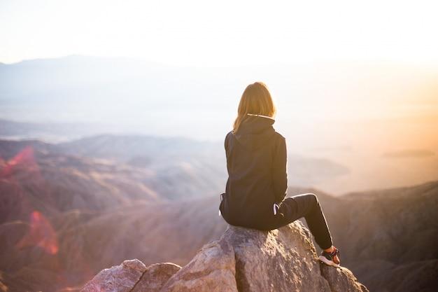 Uma mulher sentada no topo de uma montanha Foto gratuita