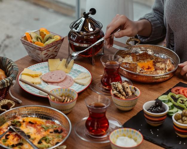 Uma mulher tomando omelete de café da manhã dentro de uma panela, em torno de uma mesa doada com azeitonas, queijo, salame, doces, legumes e chá preto. Foto gratuita