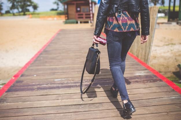 Uma mulher vai para a praia com uma ponte Foto Premium