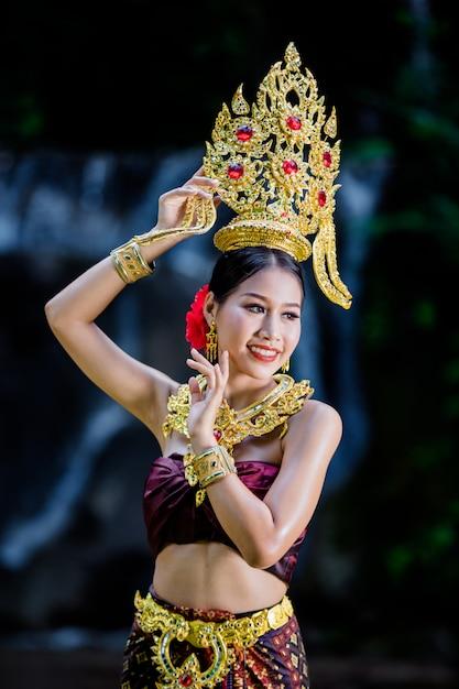 Uma mulher vestiu-se com um vestido tailandês antigo na cachoeira. Foto gratuita