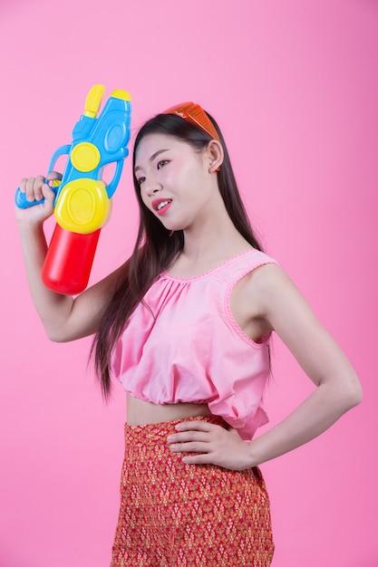 Uma mulher vestiu-se em uma roupa popular tailandesa tradicional que guardara uma arma de água em um fundo cor-de-rosa. Foto gratuita