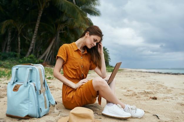 Uma mulher viaja com um laptop ao longo do oceano ao longo da areia com palmeiras Foto Premium