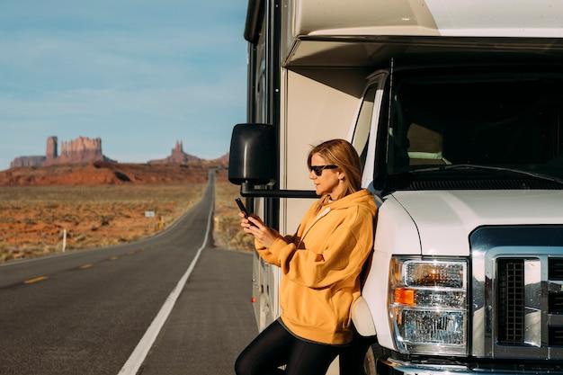Uma mulher viaja de motorhome pelo monument valley, no deserto dos eua, e verifica seu telefone celular estacionado na beira da estrada Foto Premium