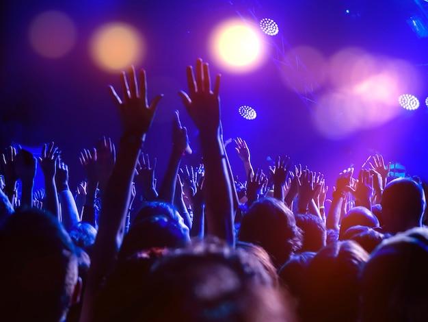 Uma multidão de pessoas na pista de dança com as mãos levantadas e luzes de discoteca Foto Premium