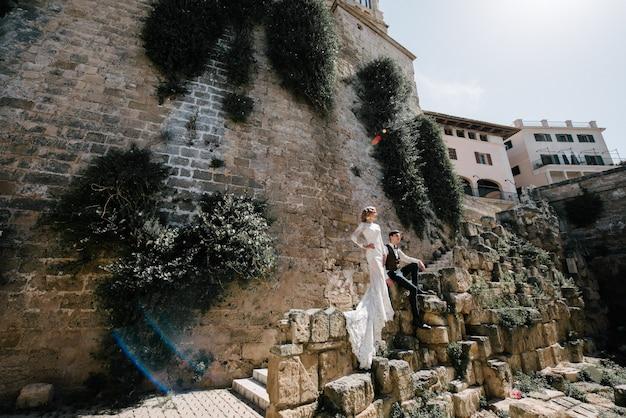 Uma noiva em um vestido branco com um buquê de flores nas mãos dela está posando Foto Premium