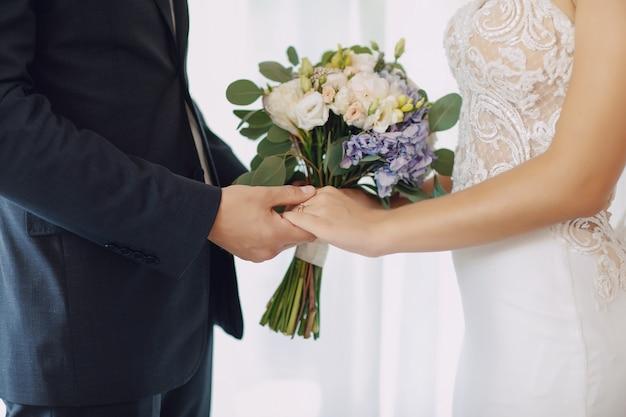 Uma noiva jovem e bonita está de pé com o marido Foto gratuita