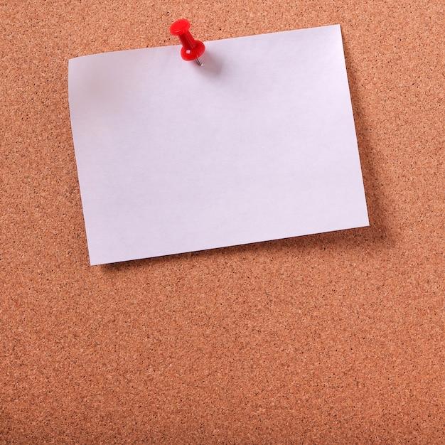 Uma nota de post-it branca fixada no espaço da cópia do quadro de avisos de cortiça Foto gratuita