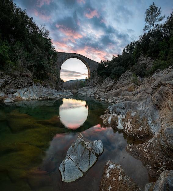 Uma paisagem surpreendente que funde o reflexo dramático do pôr-do-sol no céu de um rio entre rochas e uma ponte medieval na espanha Foto Premium