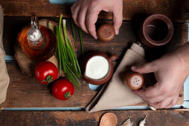 Uma panela de iogurte, tomate, ervas e azeitona em cima da mesa de madeira Foto gratuita