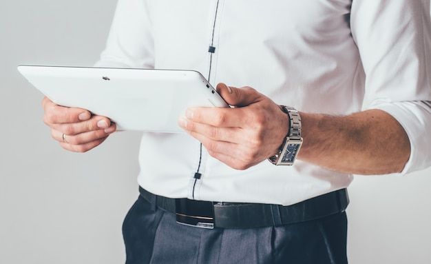 Uma pastilha branca está nas mãos de um homem. ele está de camisa branca e calça preta e lê as informações do aparelho Foto Premium