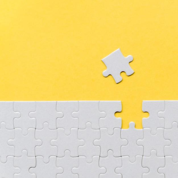 Uma peça de quebra-cabeça ausente em fundo amarelo Foto gratuita