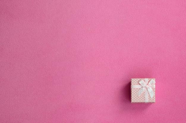 Uma pequena caixa de presente em rosa com um pequeno arco encontra-se em um cobertor de tecido de lã Foto Premium