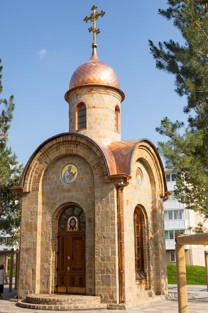Uma pequena capela da cidade feita de pedra com banhos dourados e ícones localizados no parque da cidade. Foto Premium