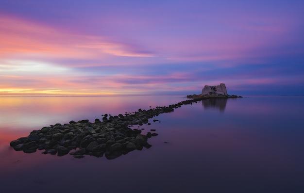 Uma pequena ilha no meio do oceano sob um céu pintado com várias cores Foto gratuita