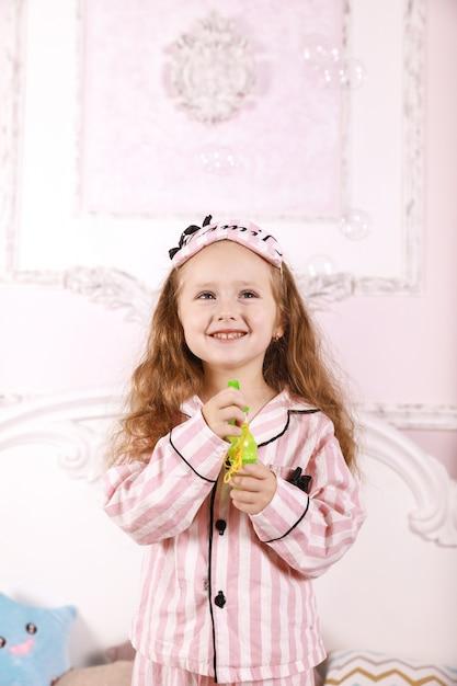 Uma pequena ruiva vestida de pijama rosa está brincando com bolhas no quarto na cama grande Foto gratuita