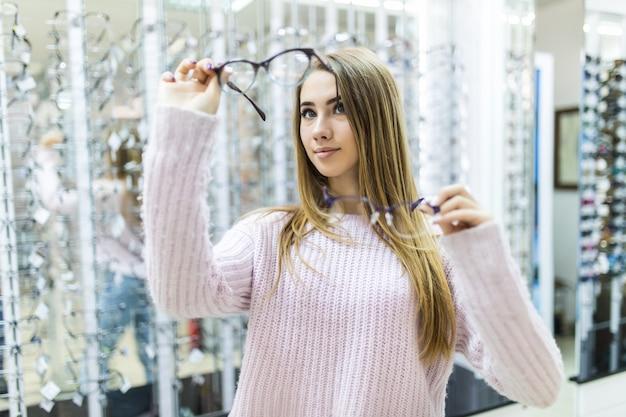 Uma pequena senhora vestida com um suéter branco segura óculos médicos no braço e os observa em uma loja especial Foto gratuita