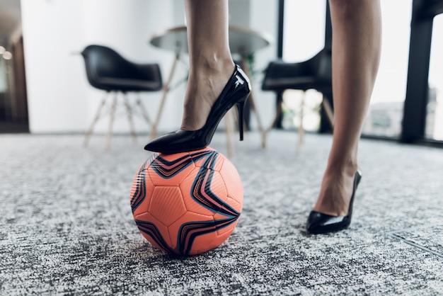 Uma perna está em uma bola de futebol laranja. Foto Premium