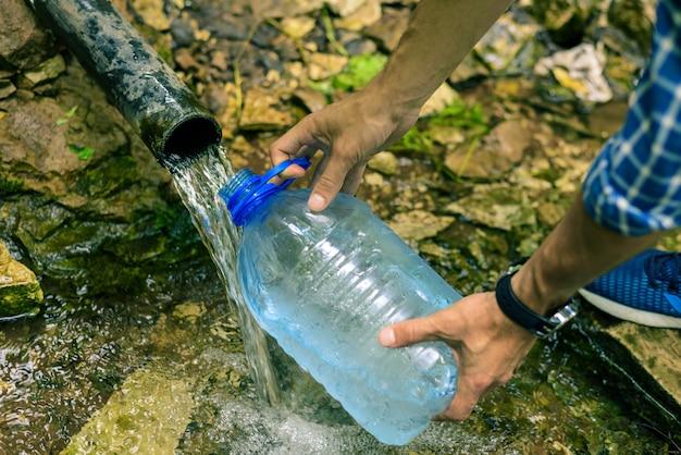 Uma pessoa coleta água limpa de uma nascente em uma garrafa de plástico Foto Premium