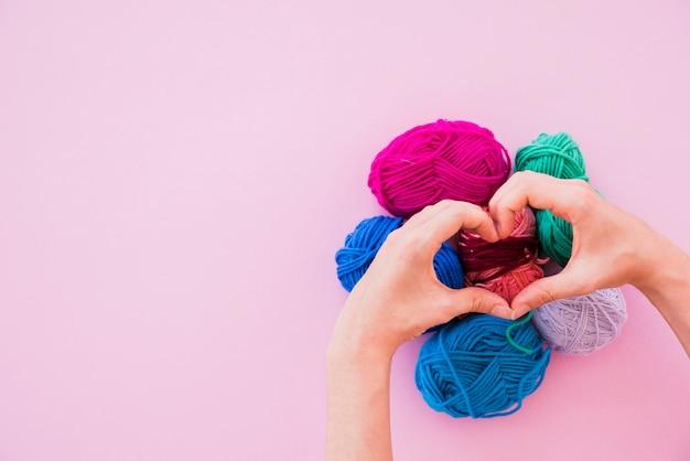 Uma pessoa fazendo coração sobre as bolas de lã coloridas no fundo rosa Foto gratuita