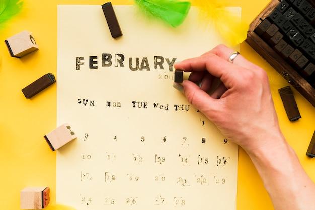 Uma pessoa fazendo o calendário de fevereiro com blocos tipográficos em fundo amarelo Foto gratuita
