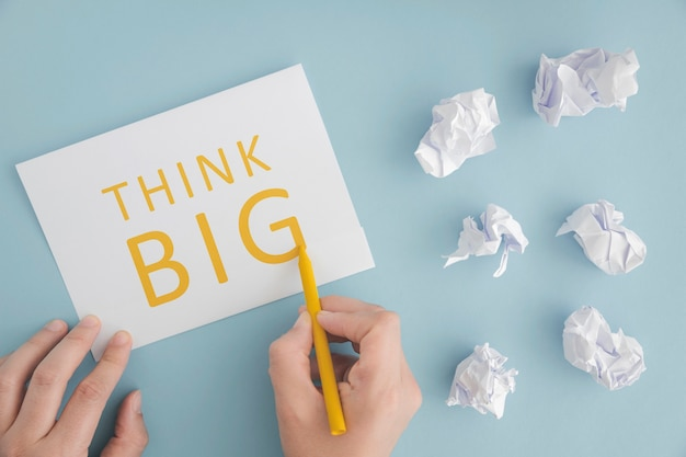 Uma pessoa que escreve pensar grande no papel com lápis amarelo sobre fundo azul Foto gratuita