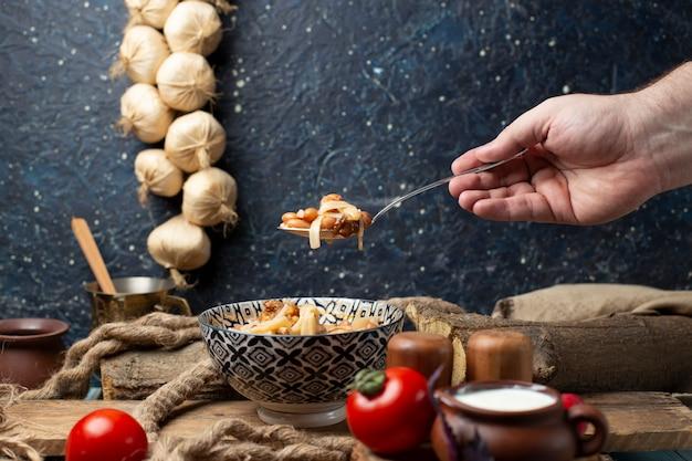 Uma pessoa que toma macarrão de feijão da tigela com colher. Foto gratuita
