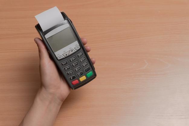 Uma pessoa segura na mão um terminal para pagar compras em uma loja usando cartões bancários ou nfc Foto Premium