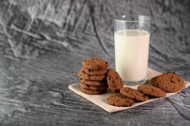 Uma pilha de biscoitos e um copo de leite em um pano sobre uma mesa de madeira Foto gratuita