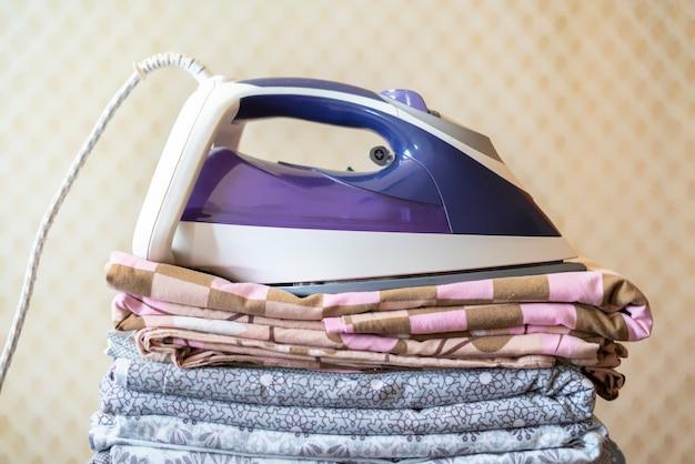Uma pilha de lençóis de cama de têxtil cobertores com ferro por cima Foto Premium