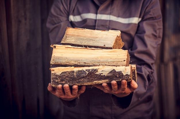 Uma pilha de lenha empilhada, preparada para aquecer a casa. homem mantém a madeira de fogo na mão. Foto Premium