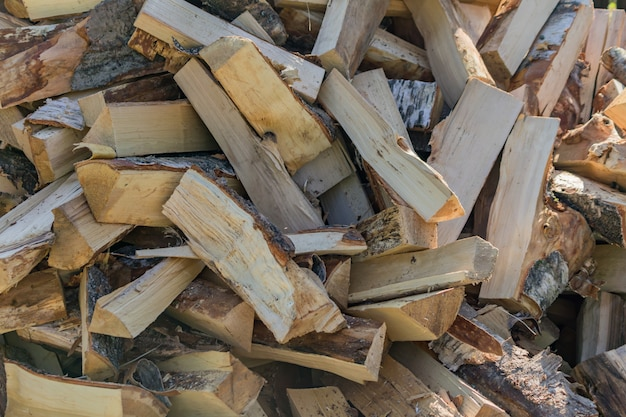 Uma pilha de lenha seca, preparada para o inverno para o aquecimento da casa. Foto Premium