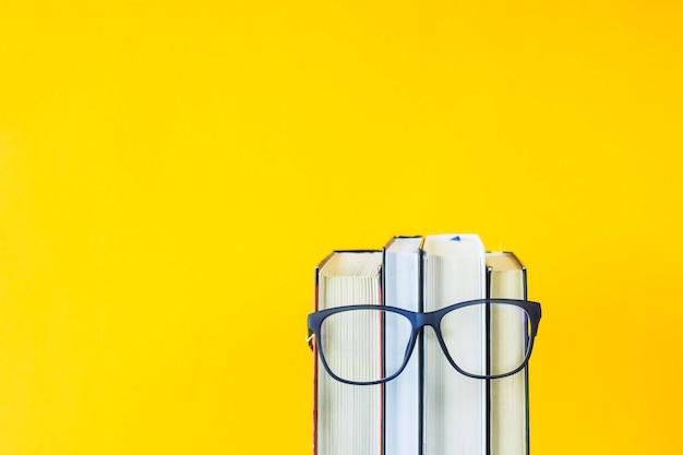 Uma pilha de livros com óculos é uma imagem do rosto de uma pessoa Foto Premium