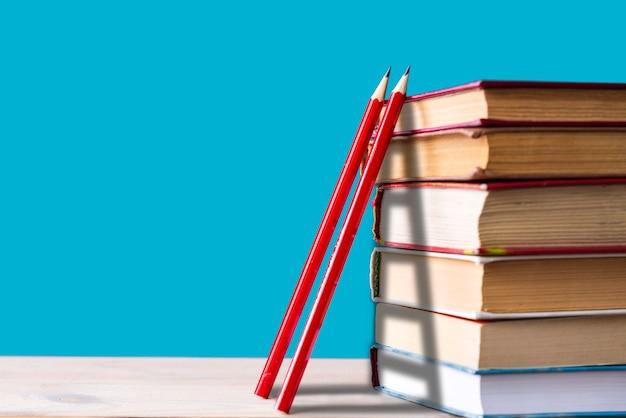 Uma pilha de livros e dois lápis de madeira vermelhos em um azul, escadas, escalando livros, obtendo conhecimento, volta às aulas Foto Premium