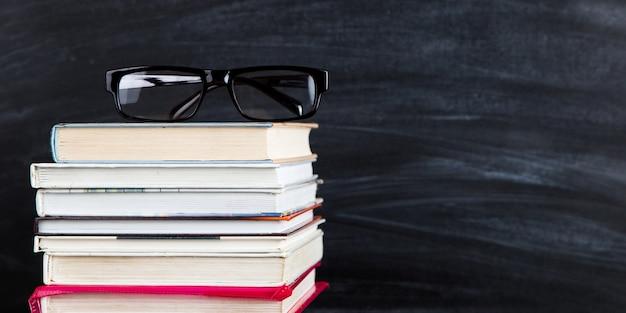 Uma pilha de livros, em cima dos óculos, contra um quadro preto, copia o espaço. Foto Premium