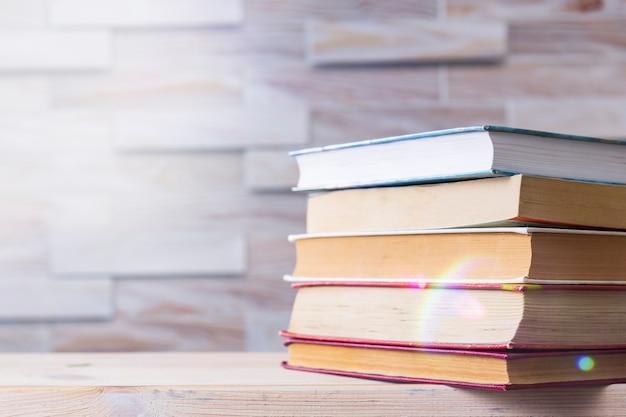Uma pilha de livros em uma mesa de madeira. de volta à escola. a auto-educação Foto Premium