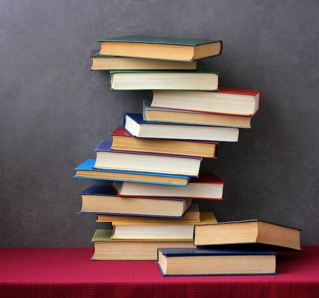 Uma pilha de livros nas capas coloridas sobre a mesa com uma toalha de mesa vermelha. ainda vida com livros. Foto Premium