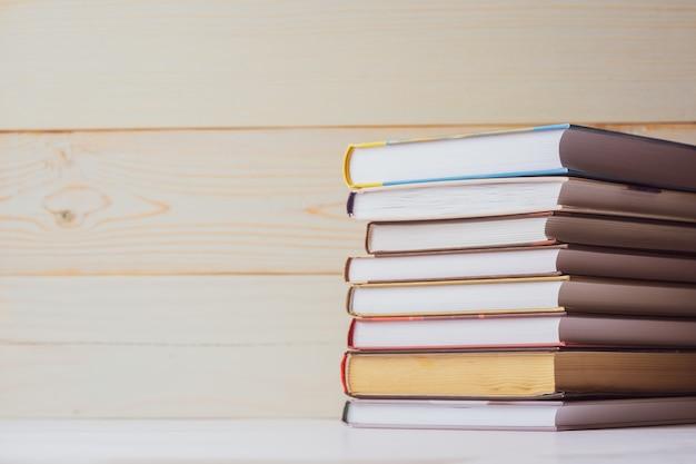 Uma pilha de livros que encontram-se na tabela em um fundo de madeira claro. de volta à escola. fundo de educação. Foto Premium