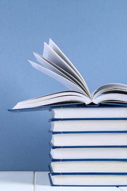 Uma pilha de livros sobre fundo azul. um livro escondido no topo da pilha. Foto Premium