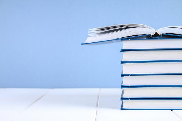 Uma pilha de livros sobre um fundo azul. um livro escondido no topo da pilha Foto Premium
