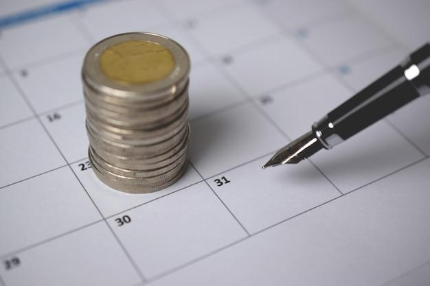 Uma pilha de moedas e uma caneta no calendário. Foto Premium