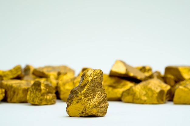 Uma pilha de pepitas de ouro ou minério de ouro isolado no fundo branco, pedra preciosa ou pedaço de pedra dourada Foto Premium