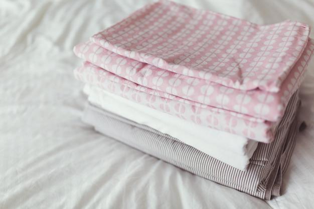 Uma pilha de roupa limpa e passada na cama Foto Premium