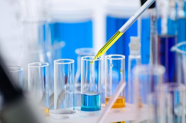 Uma pipeta soltando amostra em um tubo de ensaio, ciência abstrata Foto Premium