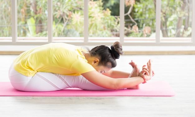 Uma professora de ioga asiática vestindo uma camisa amarela está treinando seu corpo para ser forte e saudável com o yoga. Foto Premium