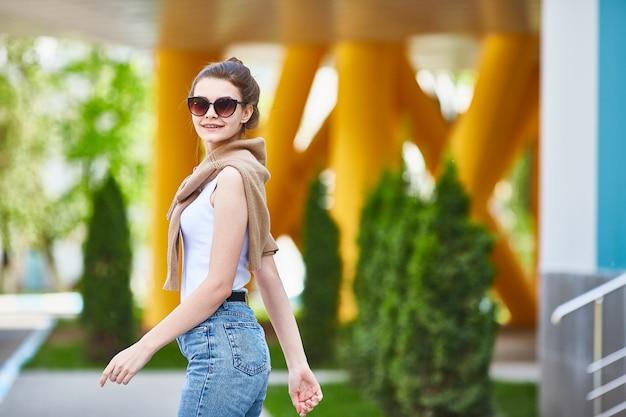 Uma rapariga anda em um dia de verão e olha para a câmera. Foto Premium