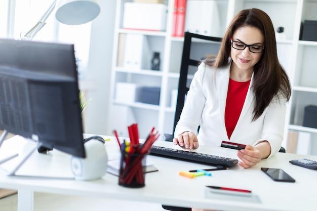 Uma rapariga que senta-se no escritório na tabela e que prende um cartão de banco. Foto Premium