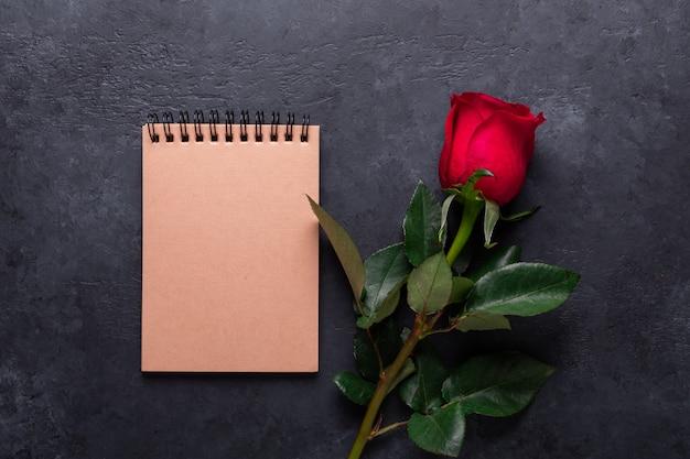 Uma rosa vermelha, caderno na pedra preta. nota de dia dos namorados com copyspace Foto Premium