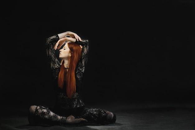 Uma ruiva atraente em lingerie preta posa no estúdio Foto gratuita